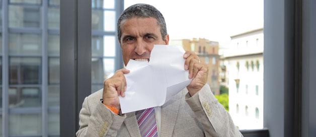 Homme qui déchire une feuille de papier avec ses dents